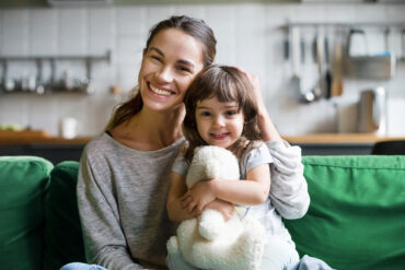 Portrait of happy family single mother and kid daughter embracing